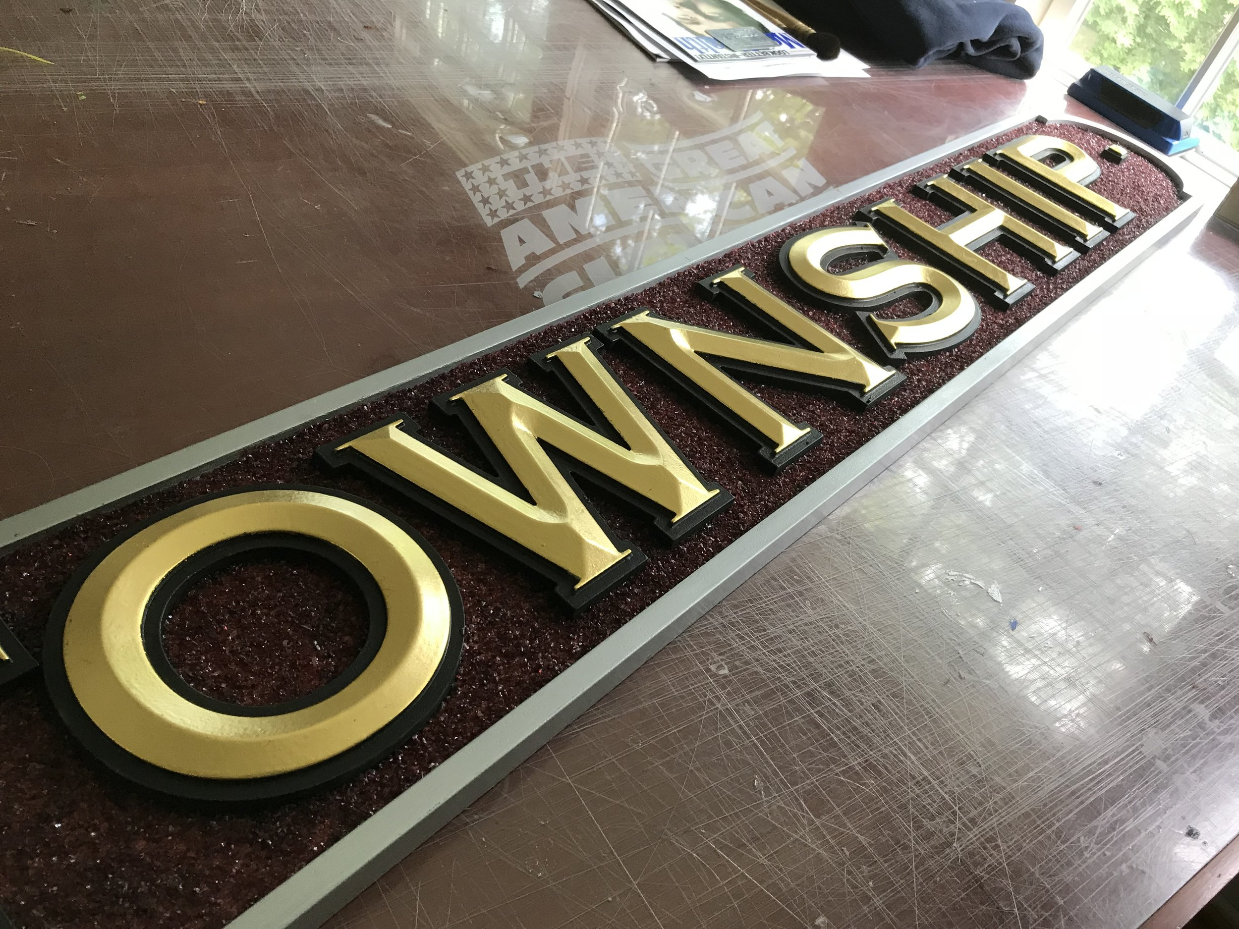 Our custom sign for Chatham FD is ready for installation with the completion of the CHATHAM TOWNSHIP wings. They feature raised prismatic letters finishe in 23.5K gold leaf im-orted from Italy against a background of crushed glass smalts from Germany. The border is palladium leaf, a tissue thin foil applied to the surface to give it a true metallic finish. With the completion of a few cut out letters, we will be ready to install.