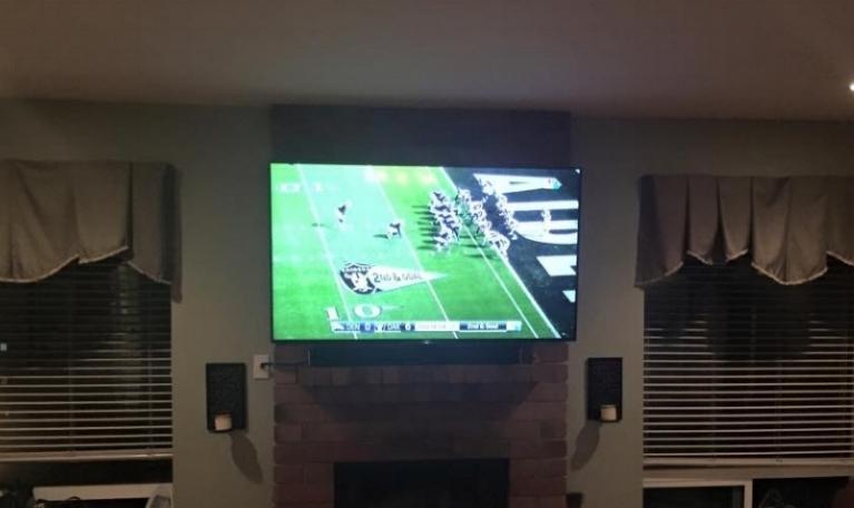 Here we hung a TV onto a brick fireplace.
