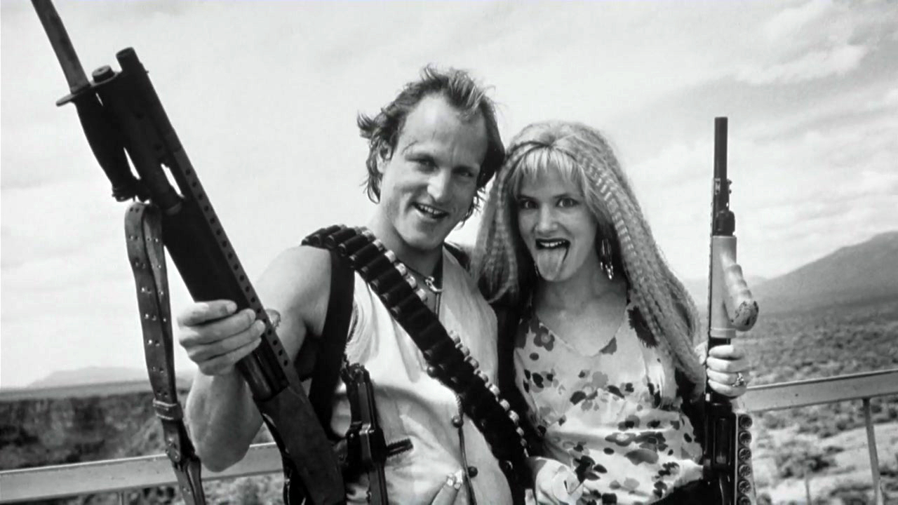 """Now if there was one project written/created by Tarantino that I wouldn't even necessarily have wanted him to direct it would be Natural Born Killers. (Not because I don't think he would've killed it, but because what we got is so unique I wouldn't want it any different.) Tarantino came up with this story about Mickey and Mallory Knox and how this serial killing couple became celebrities, which I must say is VERY """"Tarantino"""". But, when he passed it on to Oliver Stone to direct, I think that was for the best. What Oliver Stone gave us is one of the most unique films to ever grace the cinematic screen. From scenes in black and white to colorfully, psychedelic scenes to a scene that is acted out like a 50's sitcom, this film is as reckless and unpredictable as Mickey and Mallory. Now, I don't know how much of any of those ideas came from Tarantino himself, but if they didn't then I'm sure as hell glad Oliver Stone got to direct it and give us the Natural Born Killers we got to see. It's important to note, however, that without Tarantino's writing and general idea, these crazy and trippy visuals wouldn't have worked as organically as they did. It would have just been like any rap video with trippy effects for no reason at all."""