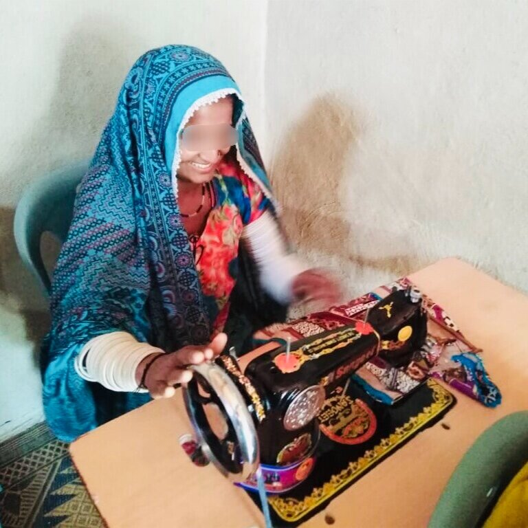 A recent student of the sewing center learns how to use a sewing machine to start her own business back in her home village.