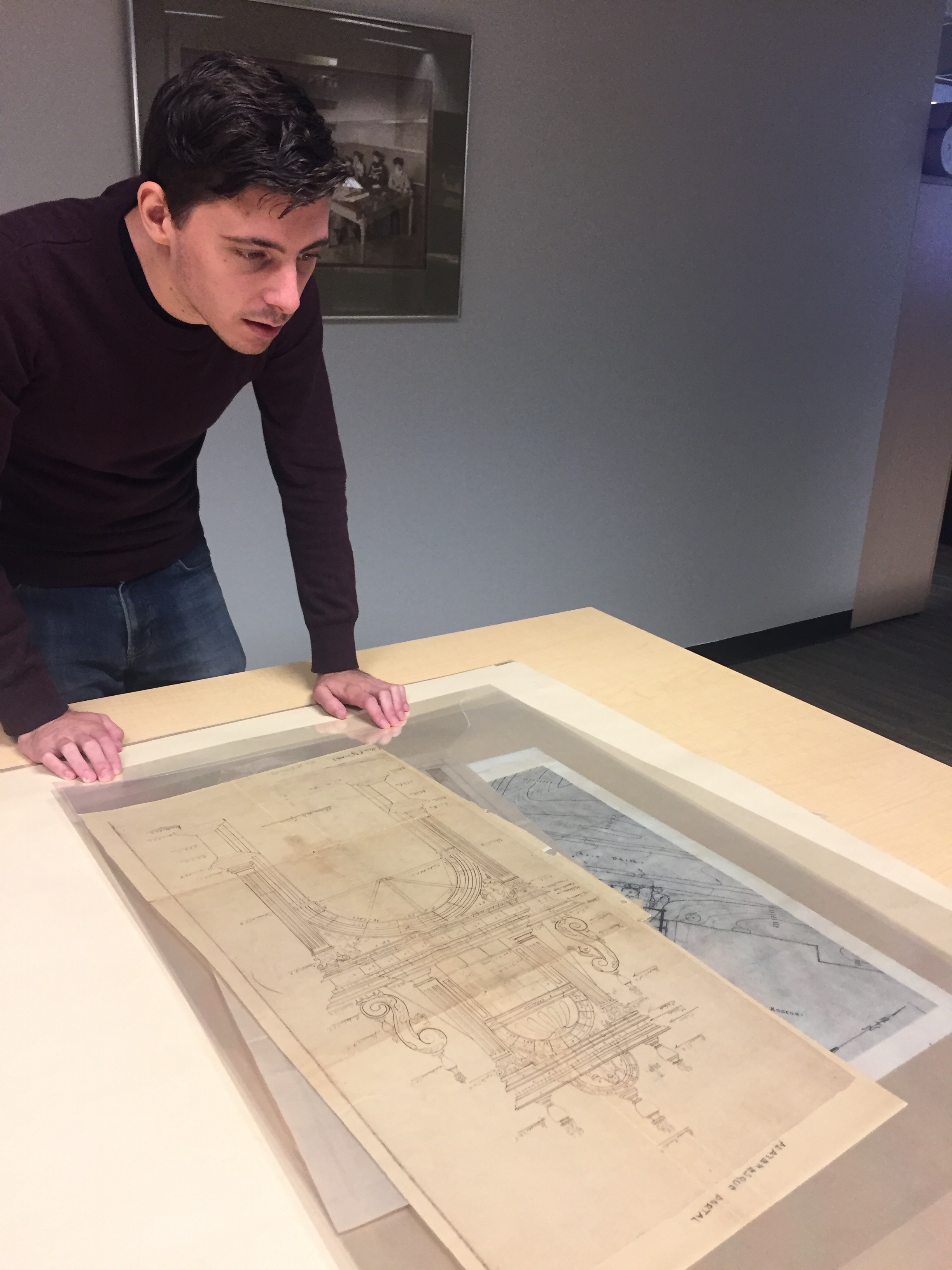 Jake examining drawings from the Julia Morgan Collection at Cal Poly