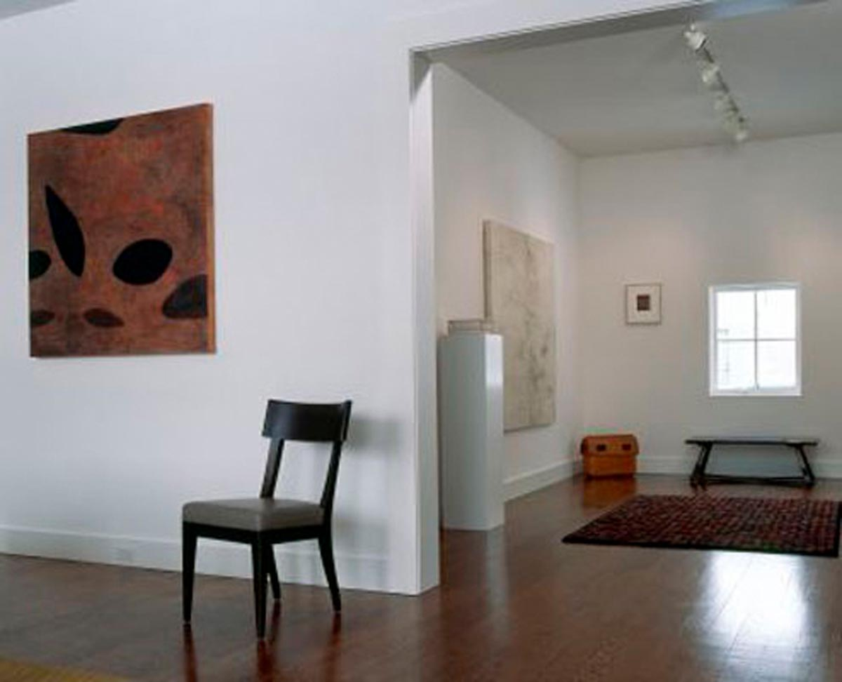 Modern entry with while walls and one wooden chair