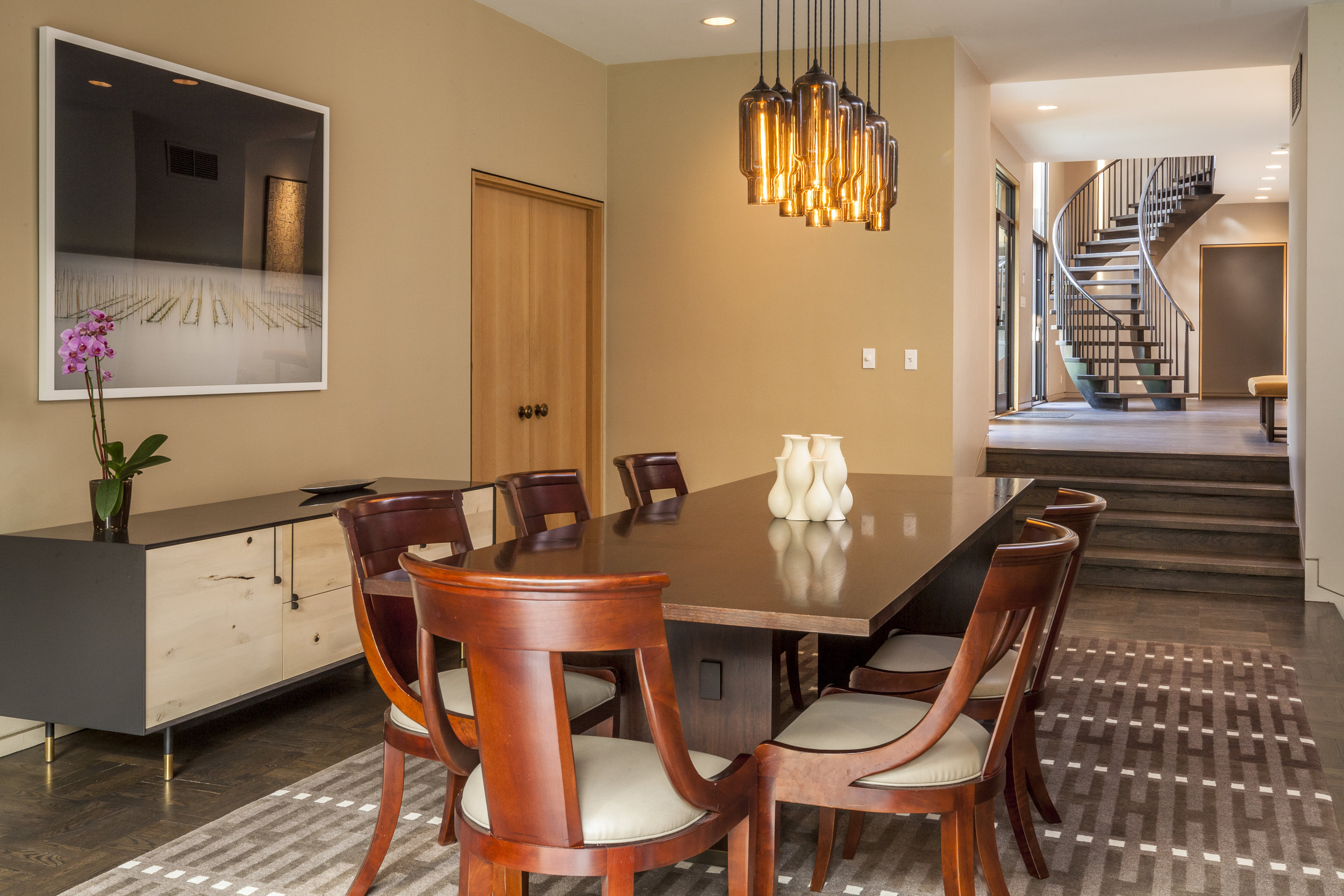 Modern dining area with large table for six with staircase in background