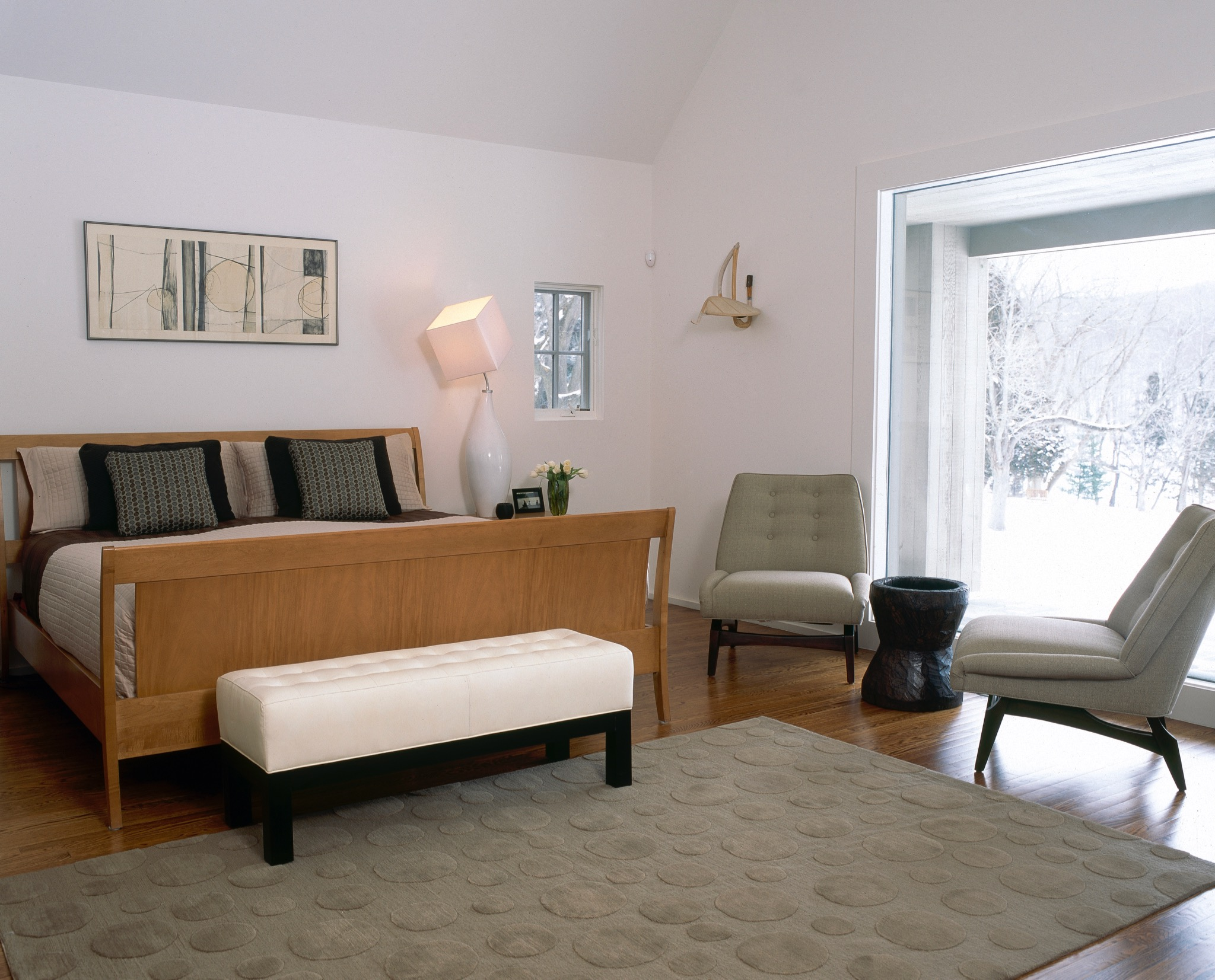 Bedroom with white walls and wooden bed in winter