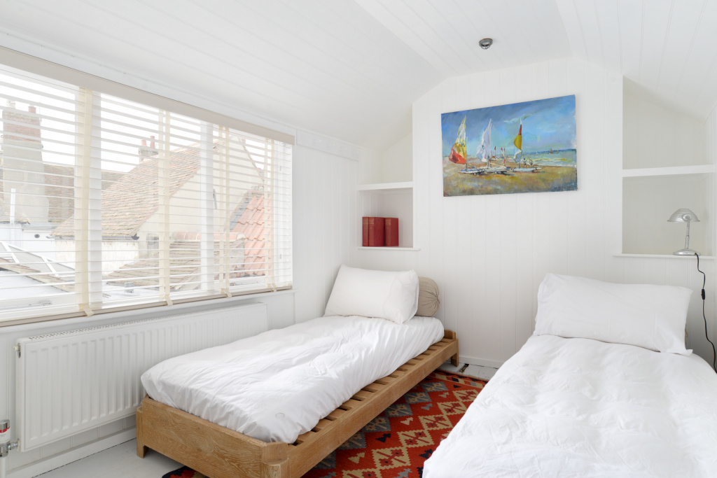 Bedrooms - Leading up from the kitchen is a secret wooden staircase leading to a wonderfully white sleeping room - this room holds an attractive Loaf day bed made from solid weathered oak that can be be used as two singles or a double. This room even has a ensuite with corner shower and wc.