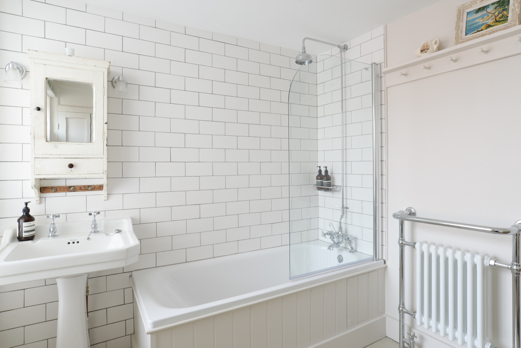 - The family bathroom, styled in contemporary white, is on this floor with a shower over the bath, sink and wc - there is a feature log wall in this space.