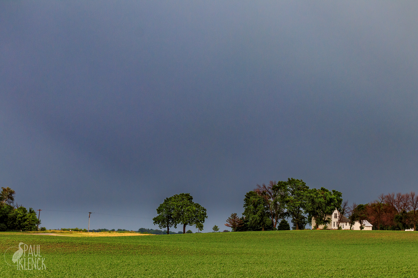 Farmhouse and soybeans under the darkening sky