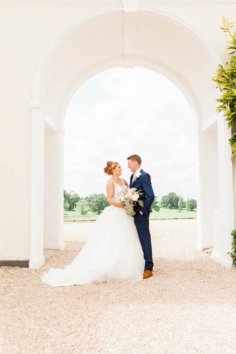 Bride and Groom stood holding hands at entrance of Rockbeare Manor