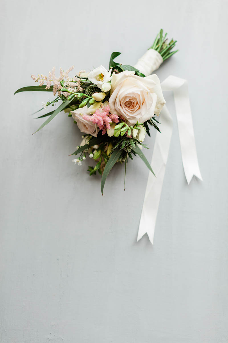 Peach and pink roses in hand tied ribbon bouquet of flowers