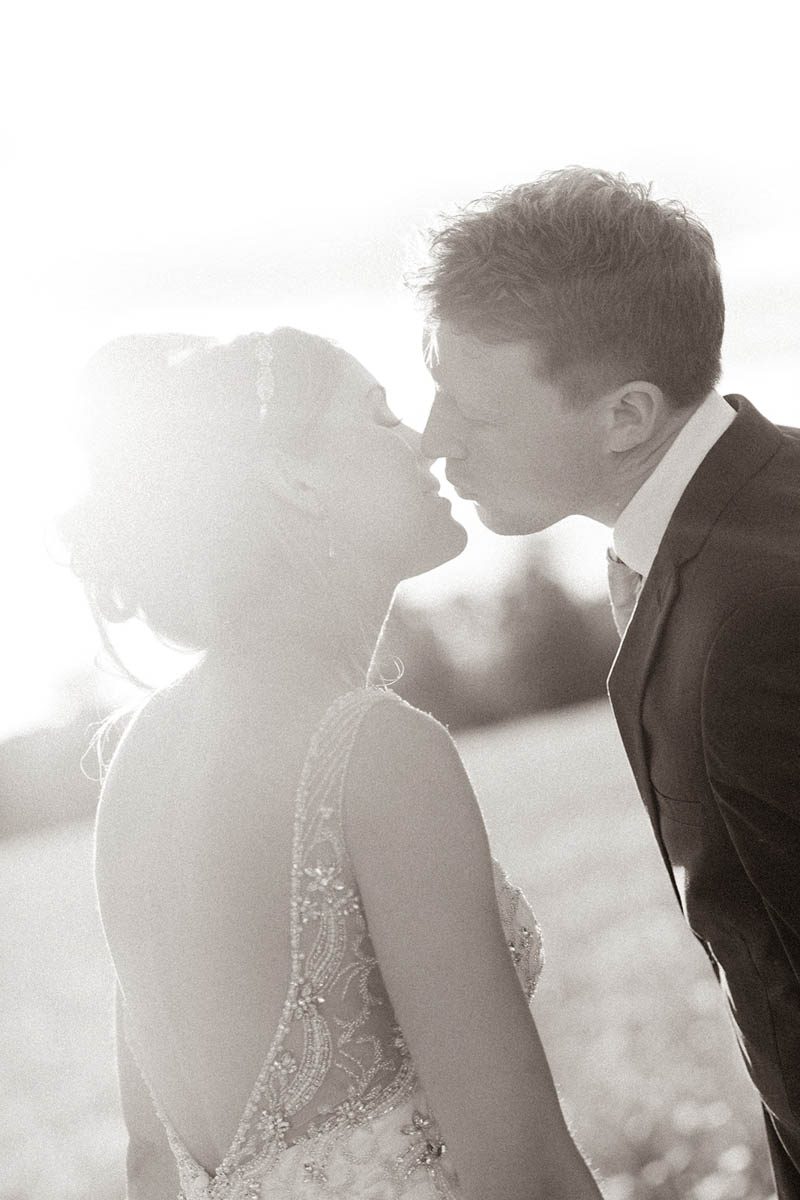 Bride and Groom on their wedding day kissing in Rockbeare Manor meadow