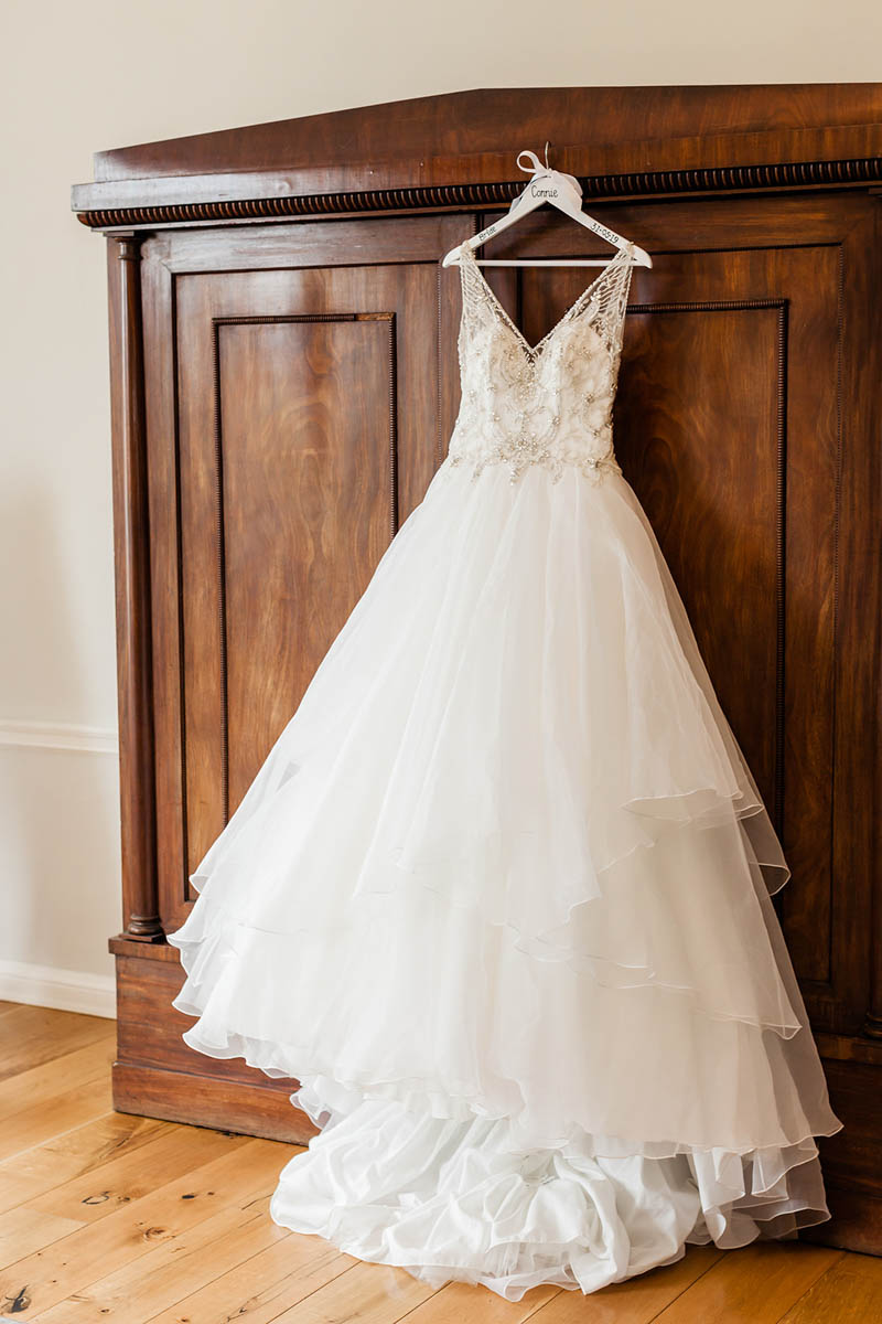 Wedding dress by designer Morilee hanging from the wardrobe at Rockbeare Manor