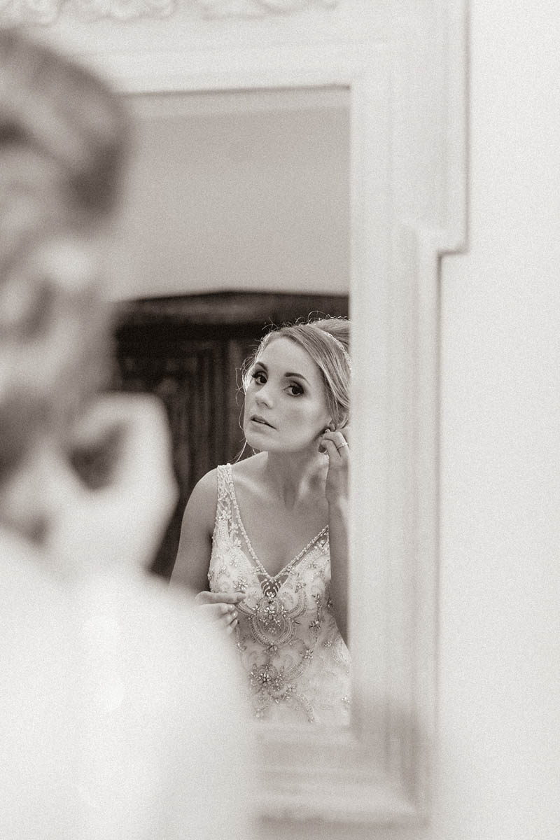 Bride checking her makeup in a gold mirror at Rockbeare Manor