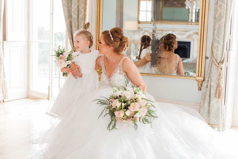Bride and her flower girl standing next to gold mirror in the bedroom at Rockbeare Manor