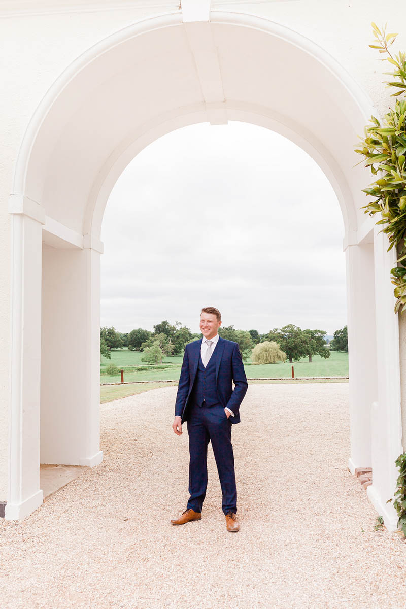 Groom wearing Ted Baker suit stood underneath white arch at Rockbeare Manor