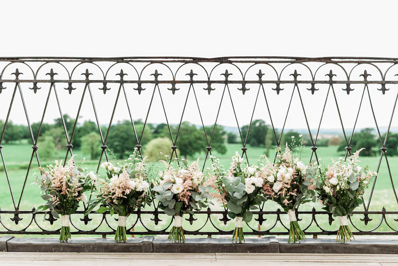 Six peach and blush rose wedding bouquets stood against the iron balcony at Rockbeare Manor