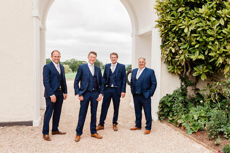 Four men in wedding day navy blue suits stood under white arch at Rockbeare Manor