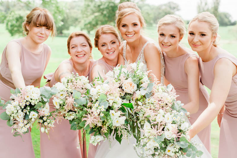 Bride and her bridesmaids holding peach and blush hand tied wedding flowers