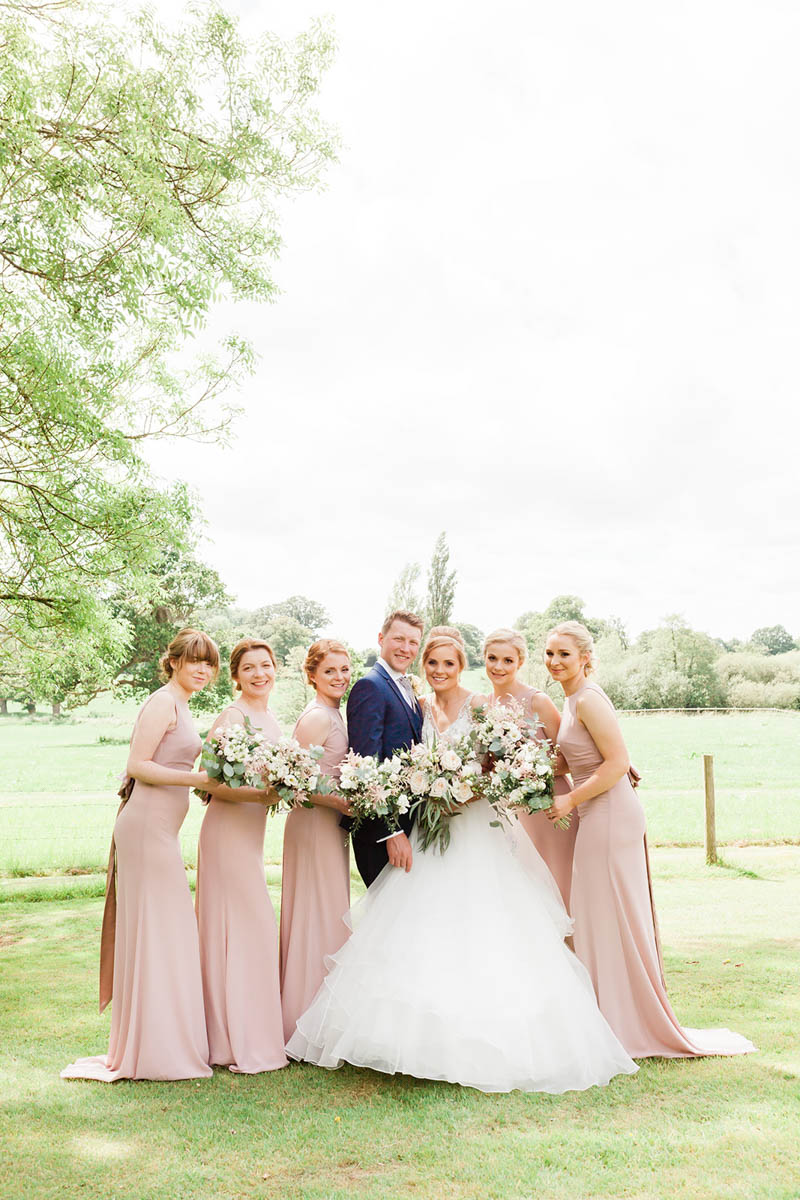 Portrait of Bride and Groom with bridesmaids in luxury wedding venue
