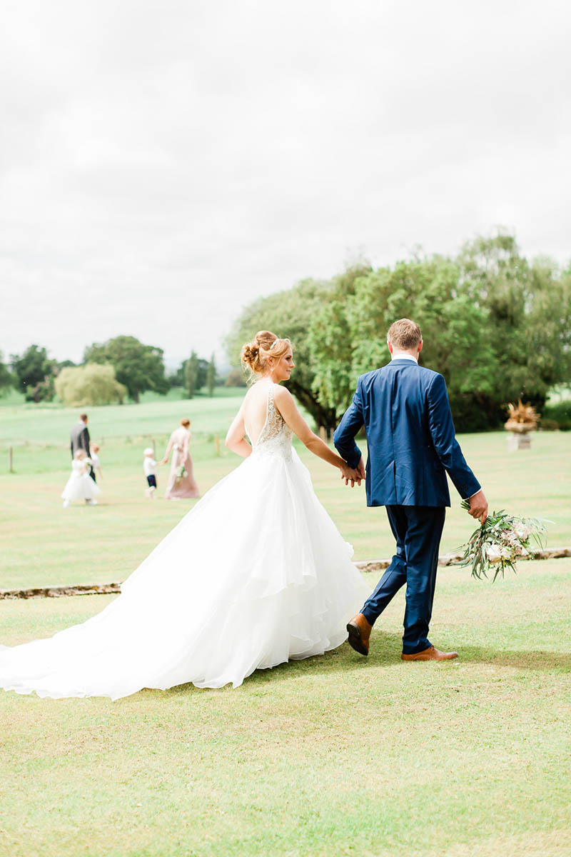 Bride walking with Groom through filed at Rockbeare Manor after their wedding