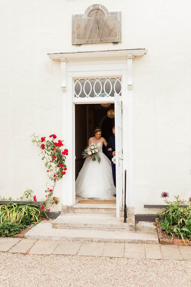 Bride walking with her father through white door to the wedding ceremony