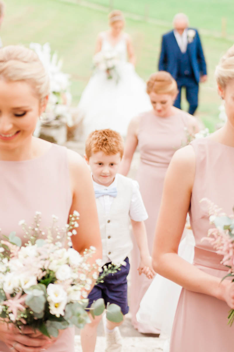 Bridesmaids walking down the aisle outside ceremony at Rockbeare Manor
