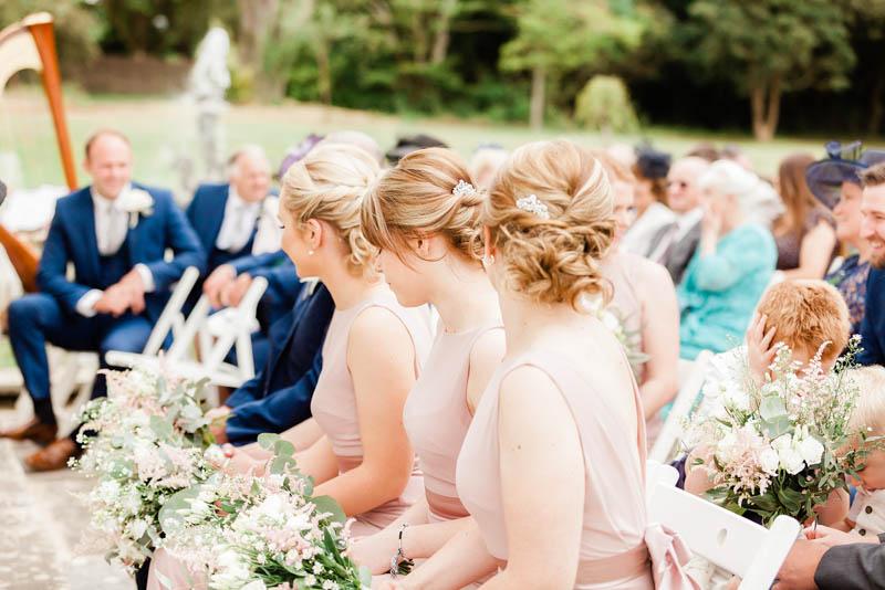 Bridesmaids wearing blush long satin wedding gowns