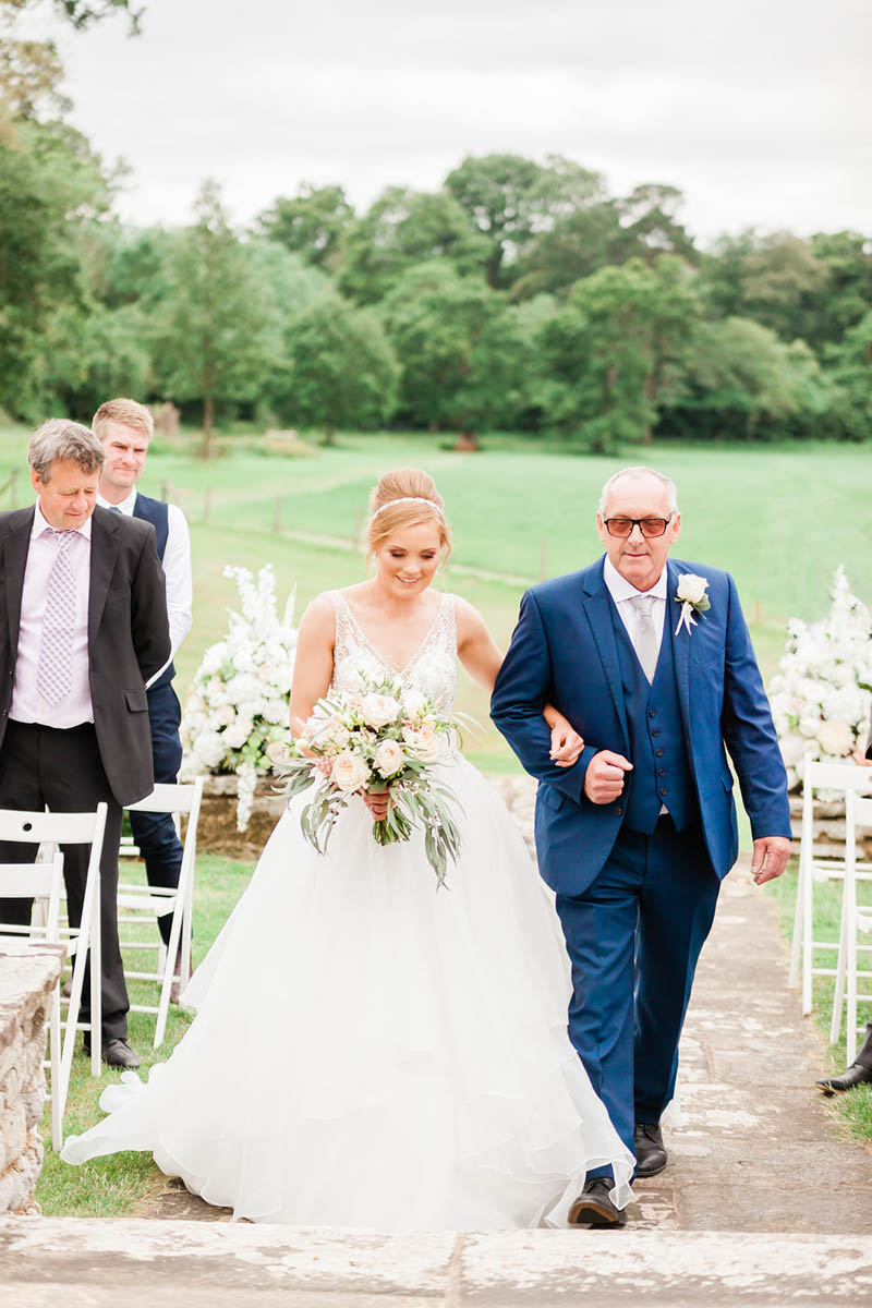 Bride with her father walking arm in arm down the aisle in Devon