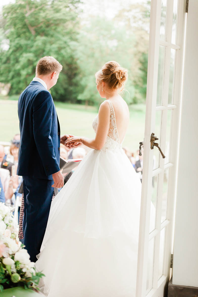Bride and groom holding hands as they exchange wedding rings at Rockbeare Manor