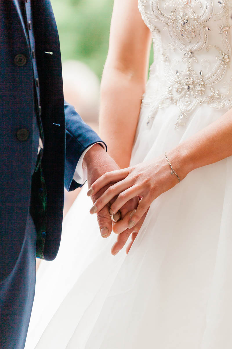 Bride holding Grooms hand against the white wedding dress