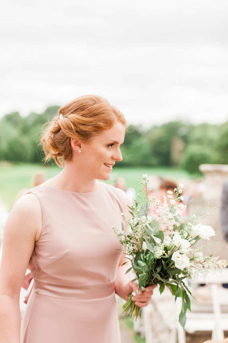 Bridesmaid wearing peach dress holding white and blush flowers hand tied with ribbon