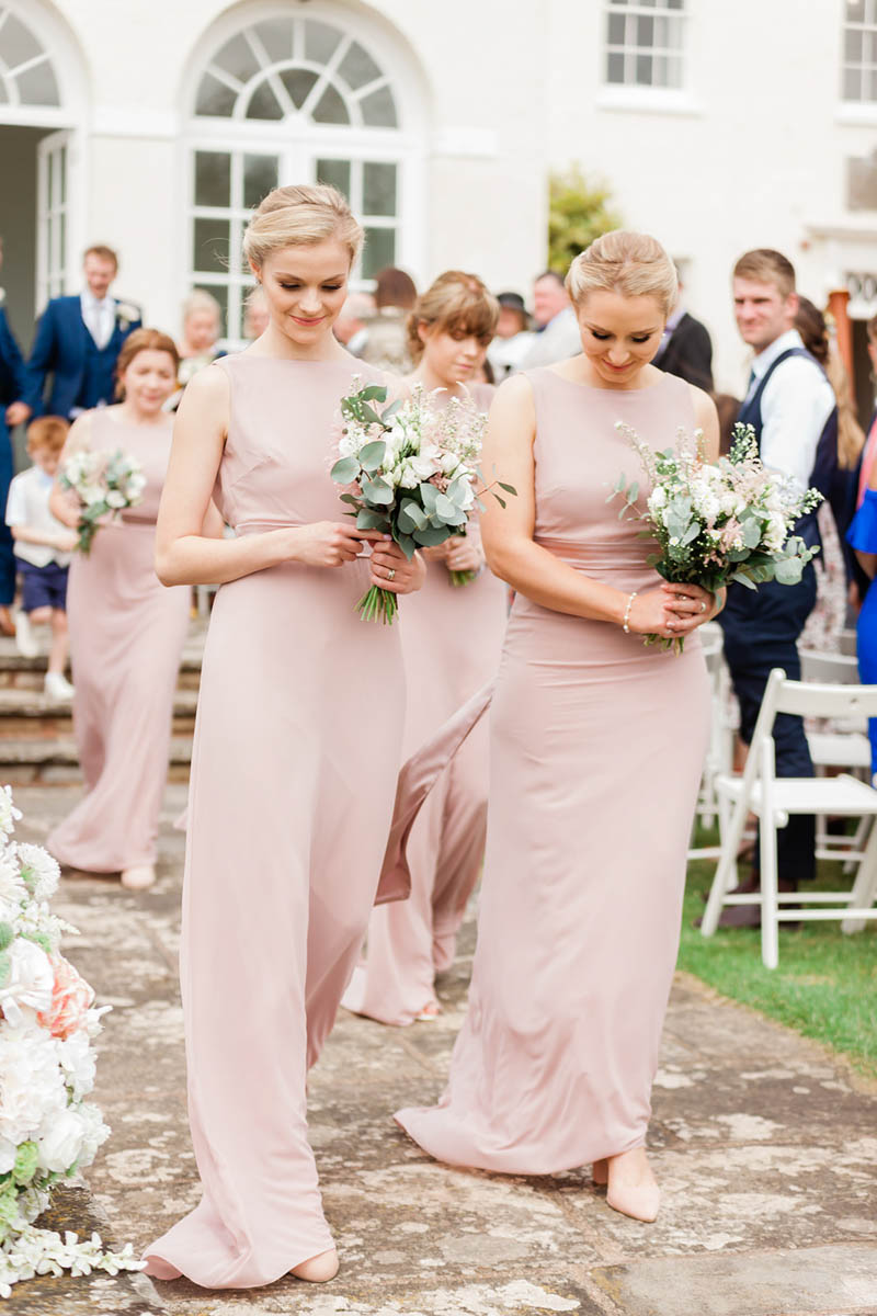 two blond bridesmaids wearing blush bridesmaids dresses at Rockbeare Manor wedding steps