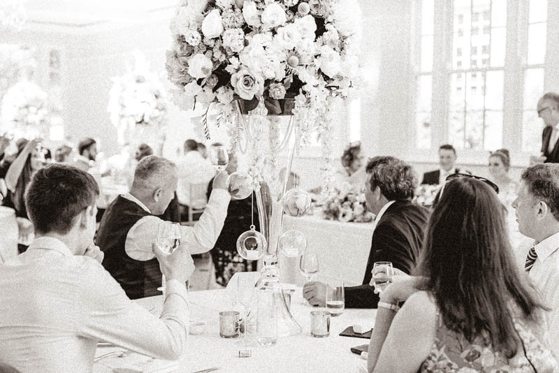 Wedding guests raising their champagne glasses to congratulate bride and groom