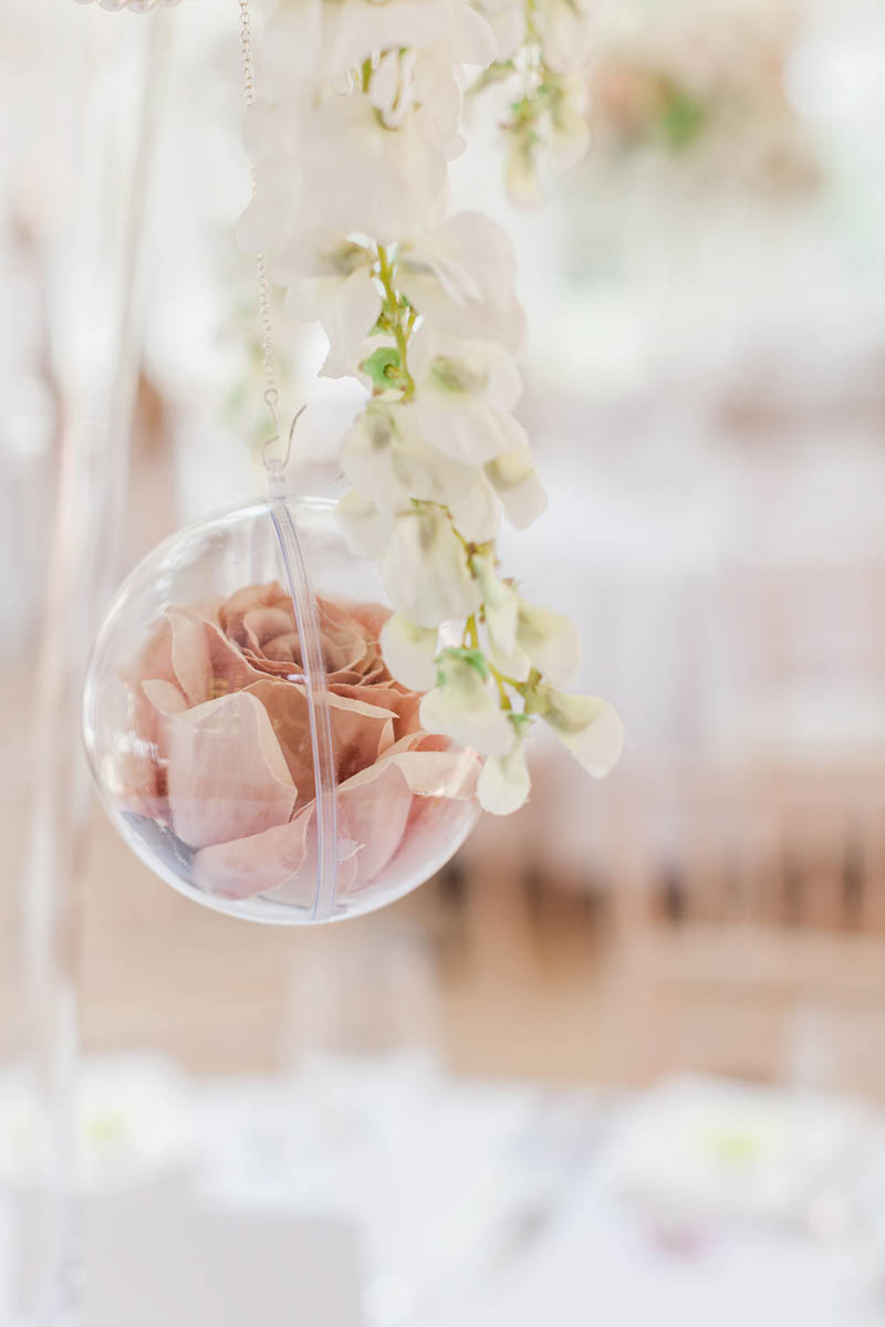 Glass bauble holding peach rose hanging over the wedding tables at Rockbeare Manor