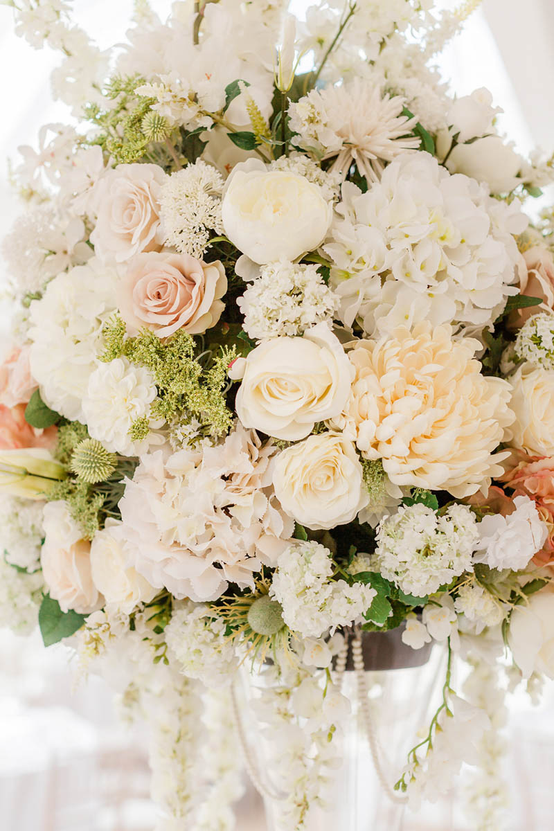 Glass vase holding hundreds of white and peach roses in the wedding dining room