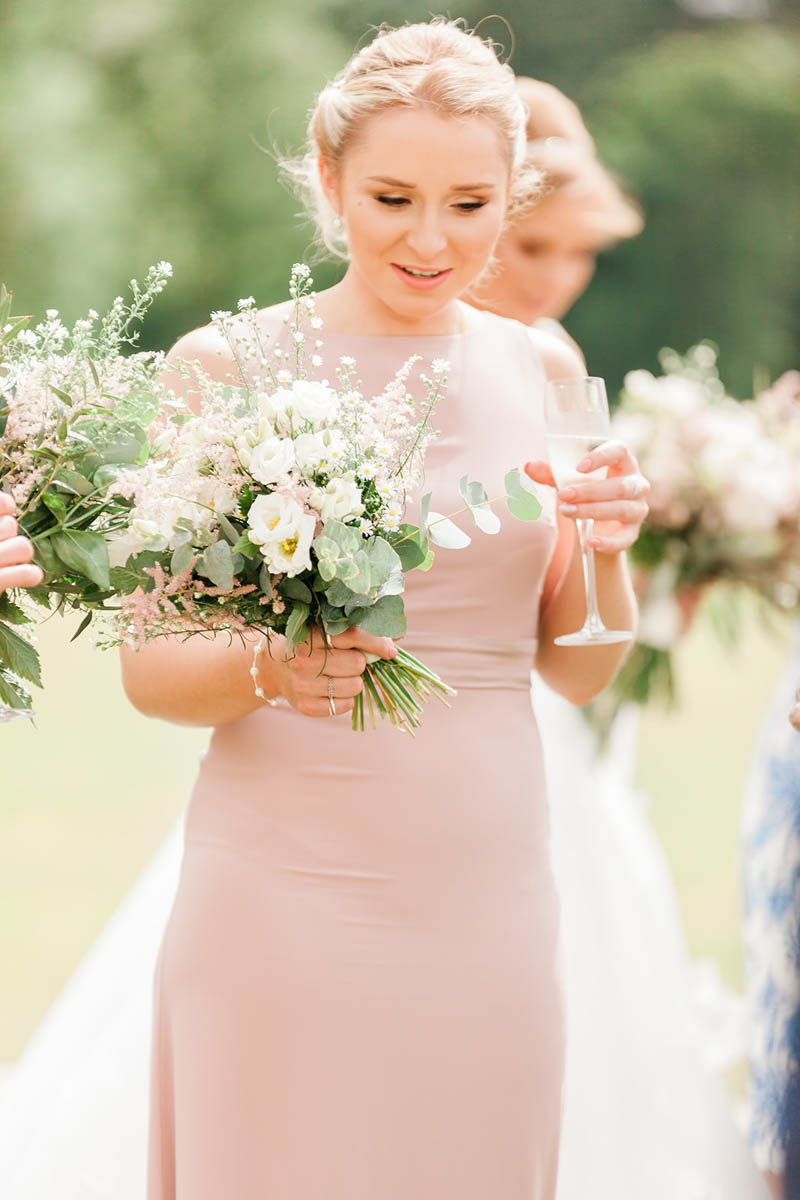 bridesmaid holding glass of Cristal champagne and smiling at Rockbeare Manor Wedding