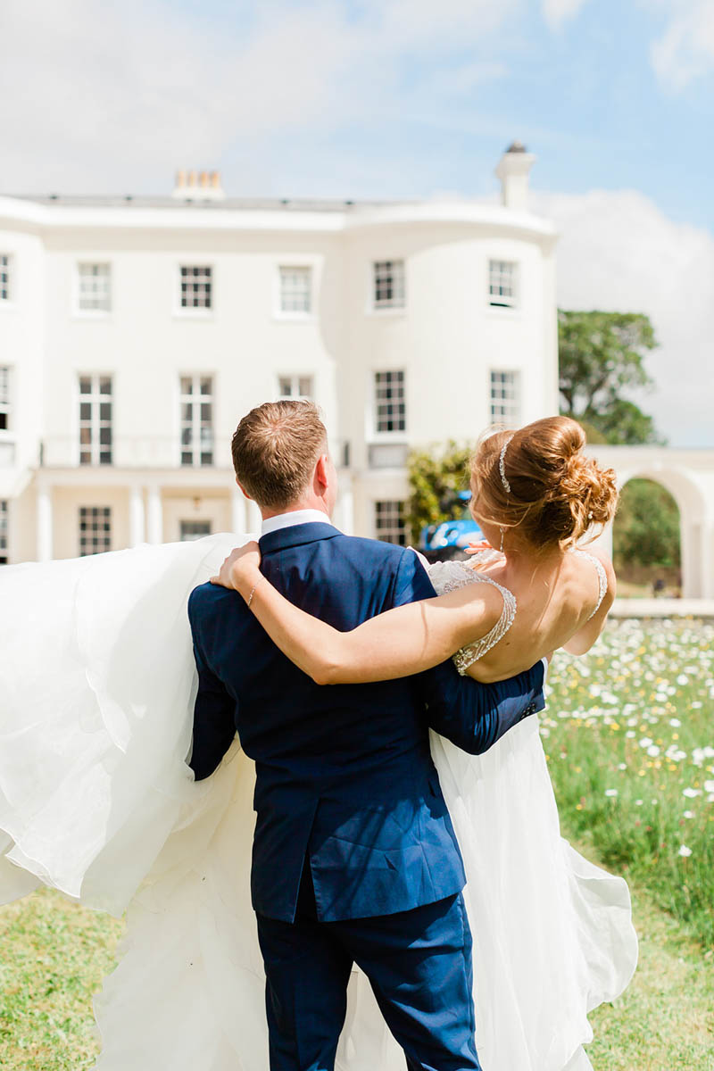 Groom carrying Bride and walking through daisy field at Rockbeare Manor in Devon