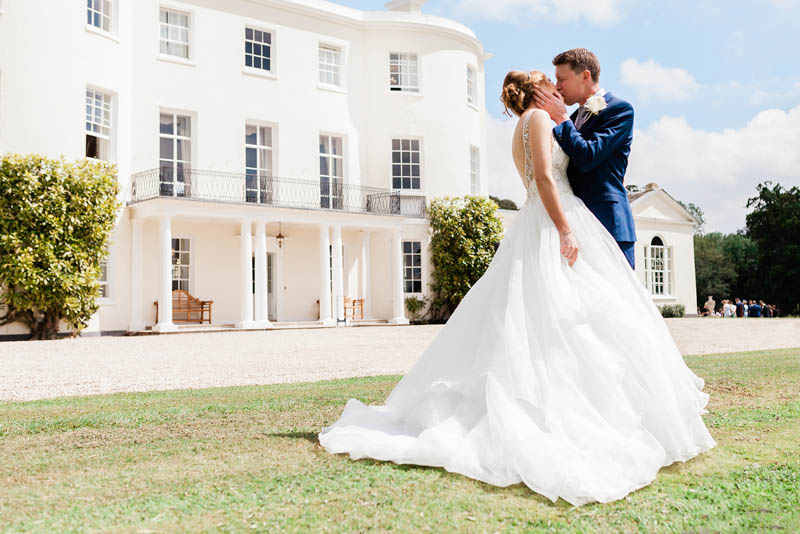 Groom kissing Bride in front of the luxury White House at Rockbeare Manor