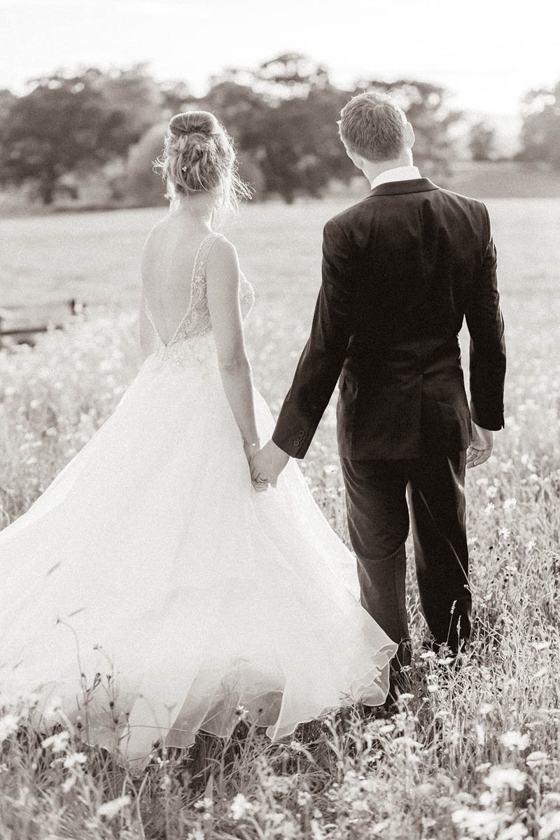 Elegant Bride and Groom walking into the sunset through meadow at Rockbeare Manor in Devon