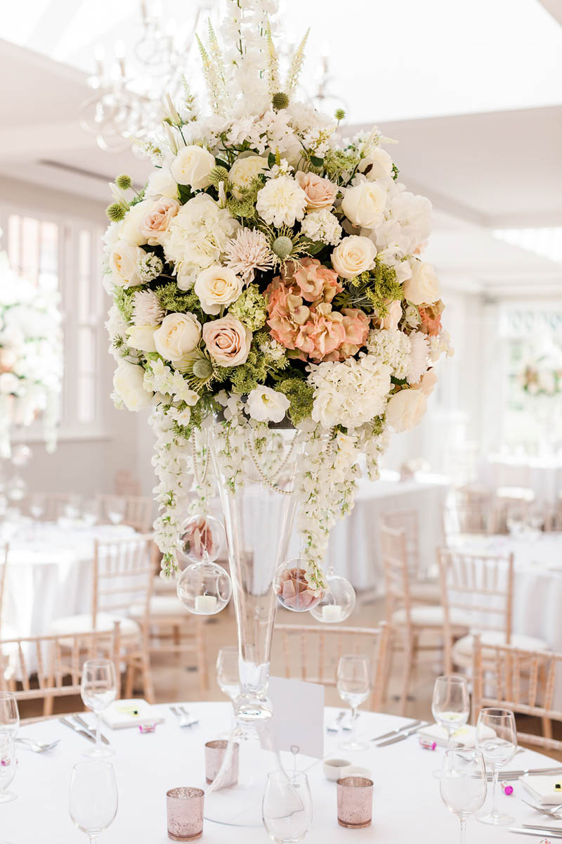 Wedding day tables with white linen and white roses in glass vase