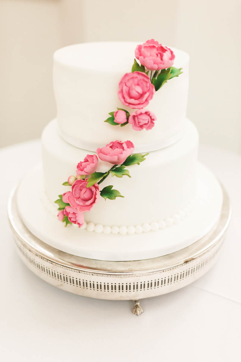 Two tiered white wedding cake with pink roses trailing across the icing at Rockbeare Manor
