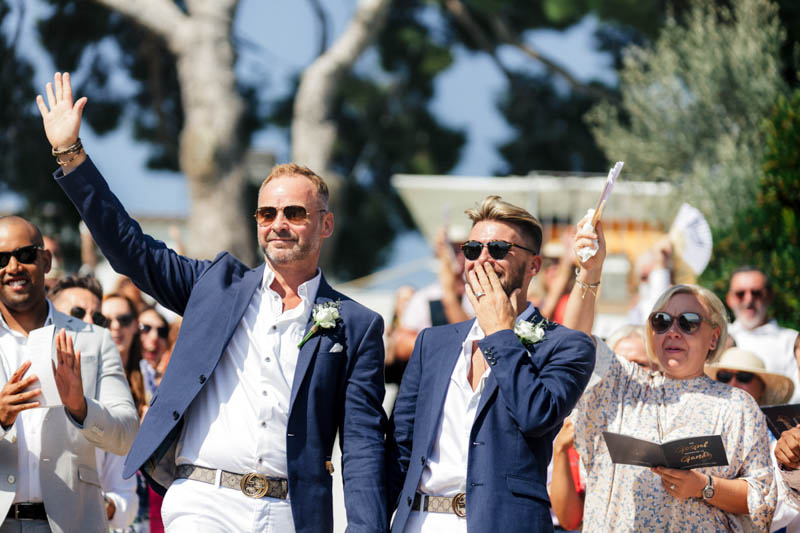 Gay men walking down the aisle holding hands at their wedding in Masia Casa Del Mar Barcelona