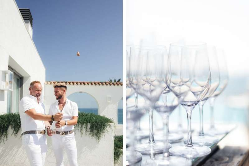 Gay couple opening champagne on the balcony of Masia Casa Del Mar in Barcelona