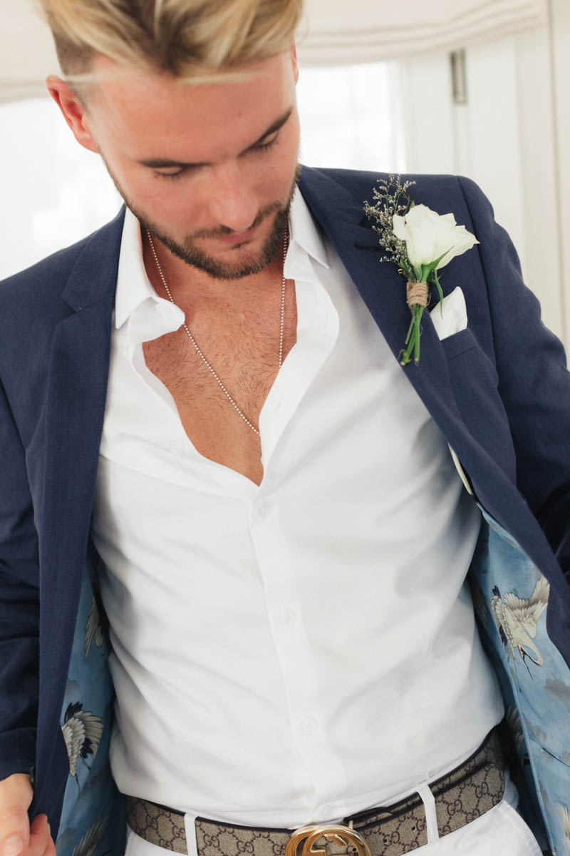 Groom wearing Gucci belt and navy blue stylish jacket with white jeans