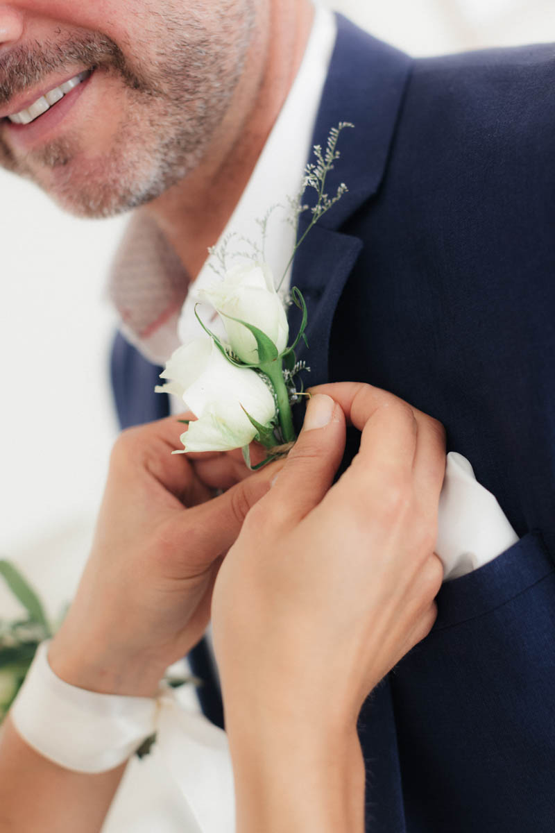 Groom wearing navy jacket having his button hole placed on his lapel