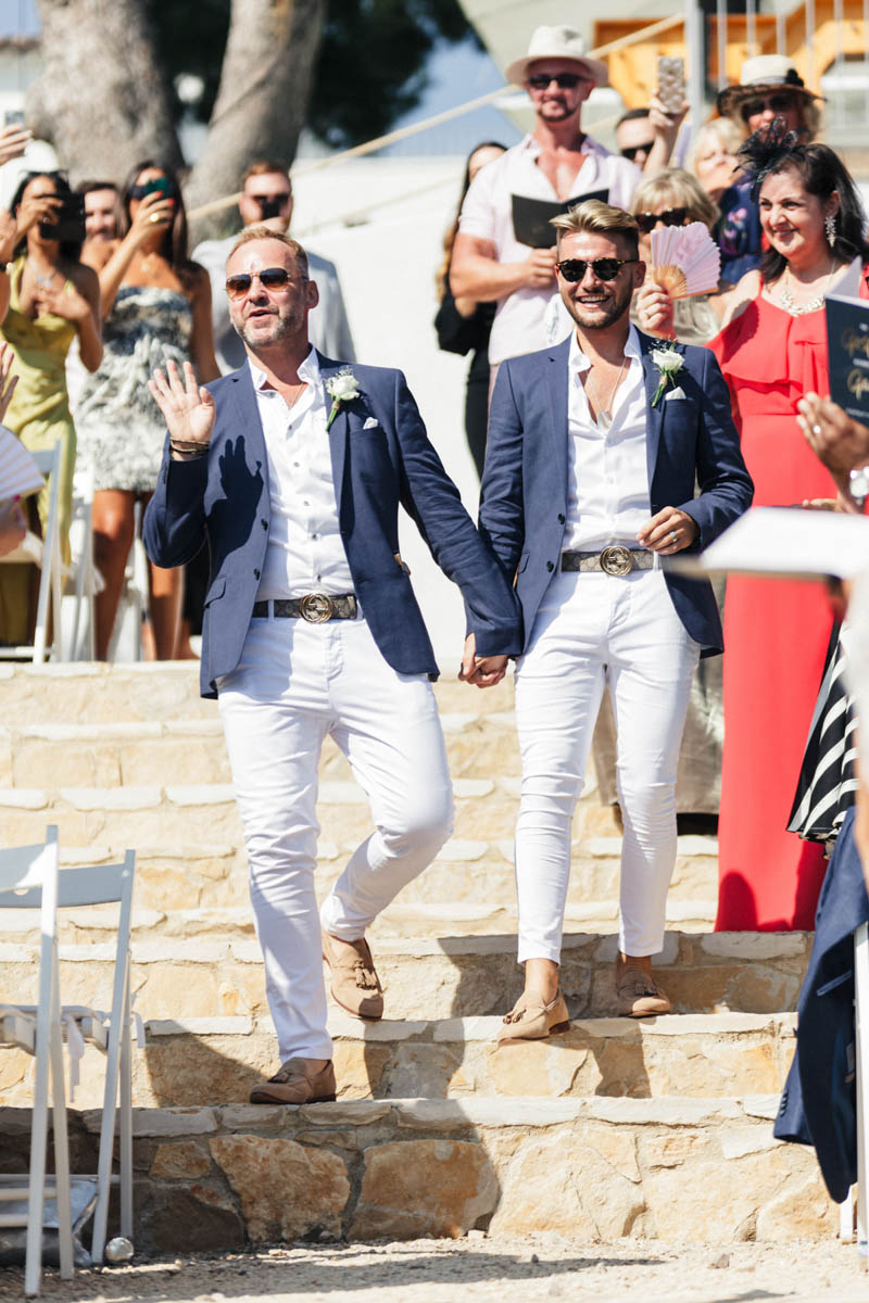 Gay couple wave to their family and friends as the walk down the stone staircase in Masia Casa Del Mar Wedding Ceremony