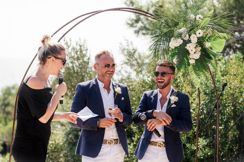 Gay couple say their vows under flower arch overlooking the sea in Sitges