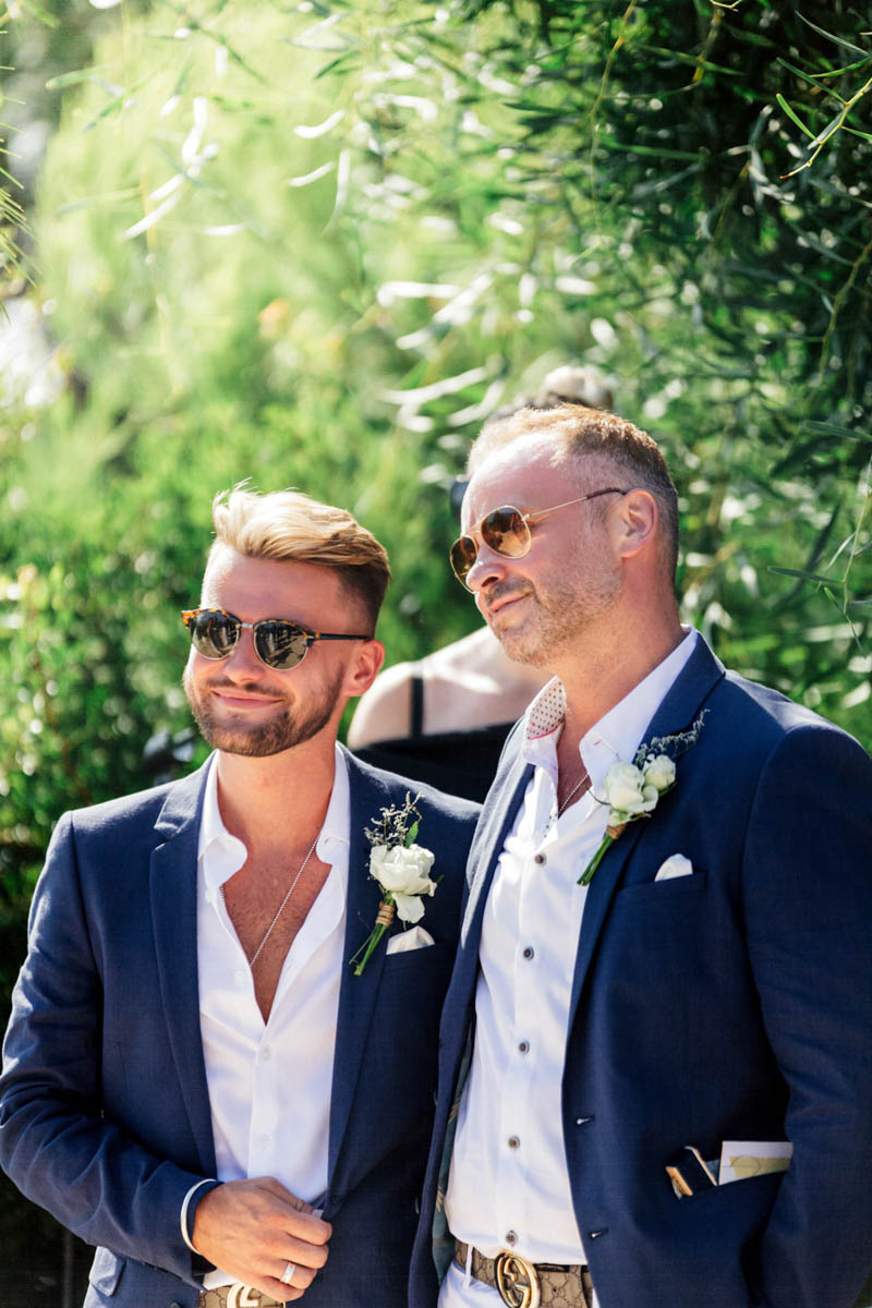 Stylish grooms wearing white trousers and shirt and navy blue jackets