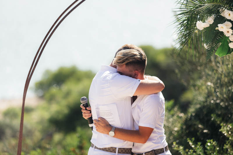 Grooms embrace as they finish saying their vows overlooking the sea at Masia Casa Del Mar