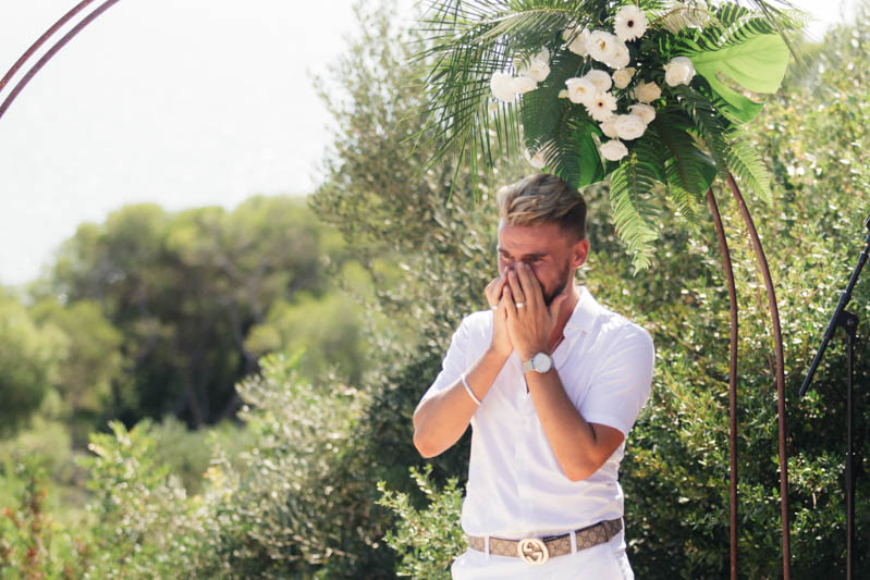Groom wiping his eyes as he cry tears on the alter at Masia Casa Del Mar Sitges