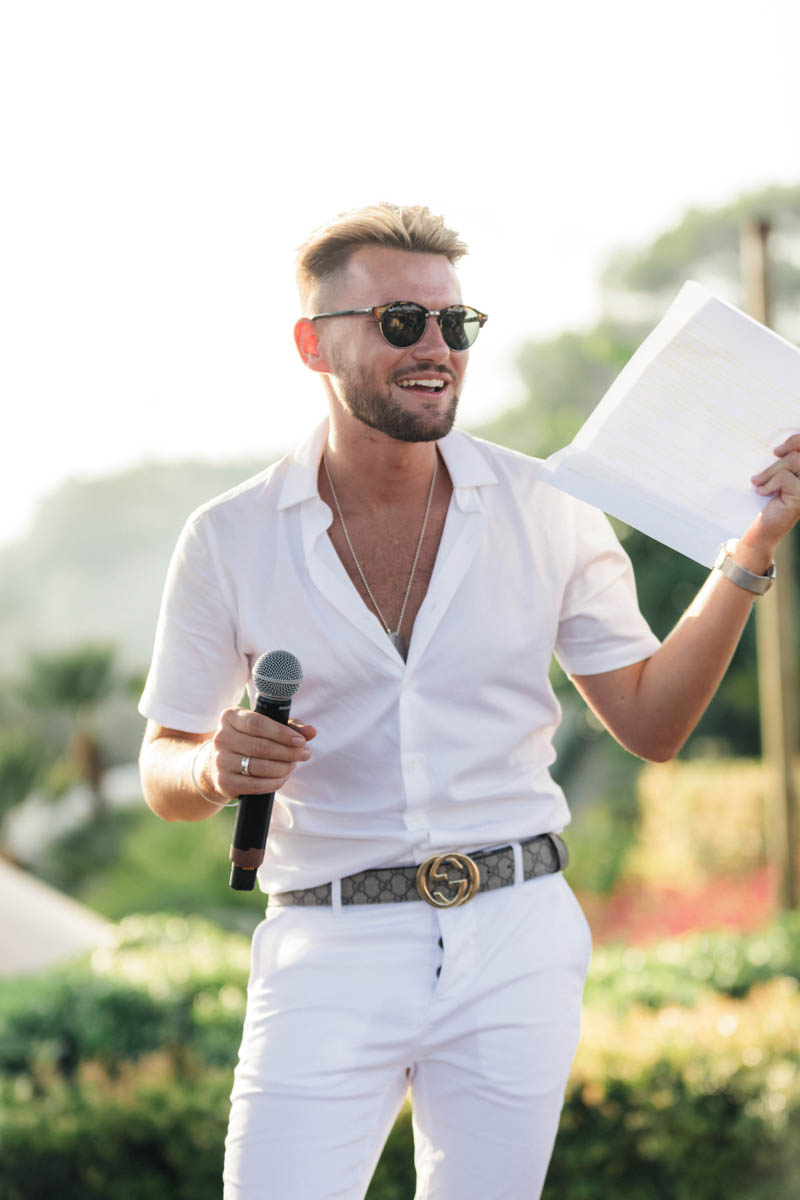 Groom wearing white jeans and shirt reading his speech in Barcelona wedding